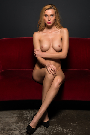 nude blonde woman: Beautiful slender Czech blonde sitting nude on a red couch
