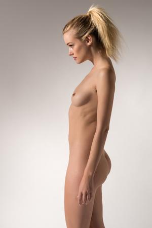 Pretty slender blonde woman nude on gray