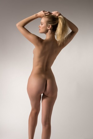 Pretty slender blonde woman nude on gray