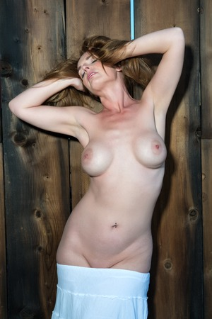 Beautiful tall redhead standing nude on a wooden door Stock Photo