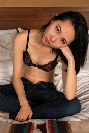bluejeans: Pretty slender Chinese woman in a pink and black bra and jeans