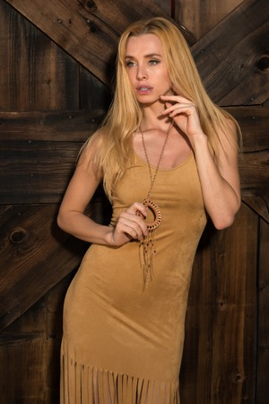 suede: Beautiful slender Czech blonde in a gold suede dress Stock Photo