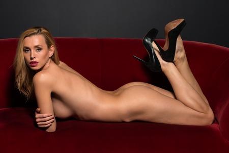 mujer rubia desnuda: Hermosa esbelta rubia Checa desnuda sentada en un sofá rojo Foto de archivo