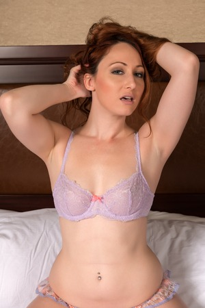 redhead lingerie: Pretty young redhead dressed in lilac lingerie Stock Photo