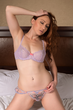 Pretty young redhead dressed in lilac lingerie Stock Photo