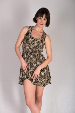 mujeres morenas: joven morena escultural con un vestido estampado de leopardo