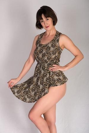Statuesque young brunette in a leopard print dress
