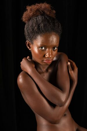 Petite Rwandan woman sitting nude on black Stock Photo