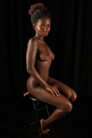 Petite Rwandan woman sitting nude on black Stock Photo