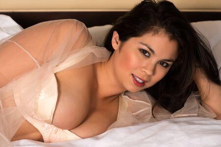 Beautiful young Eurasian woman in beige lingerie photo