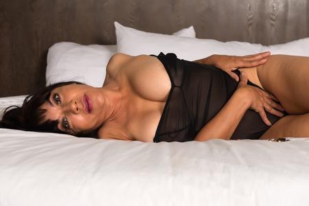 donne mature sexy: bruna abbastanza matura in un body marrone Archivio Fotografico