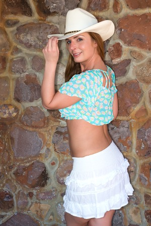 rockwall: Beautiful tall redhead in a midriff blouse and white skirt Stock Photo