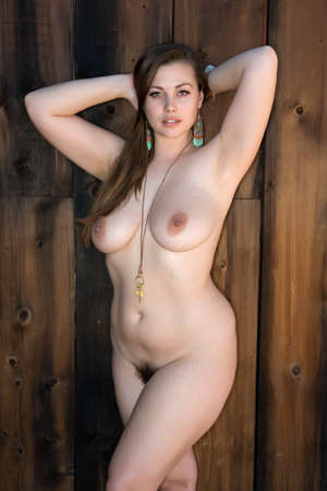 Pretty shapely brunette standing nude against a wooden door
