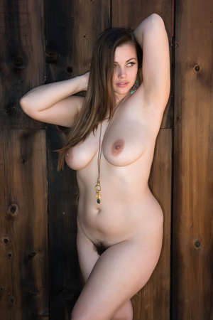 nudity: Pretty shapely brunette standing nude against a wooden door