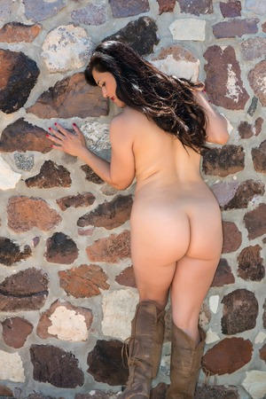 naked girl black hair: Pretty mature Eurasian woman nude on a rock wall