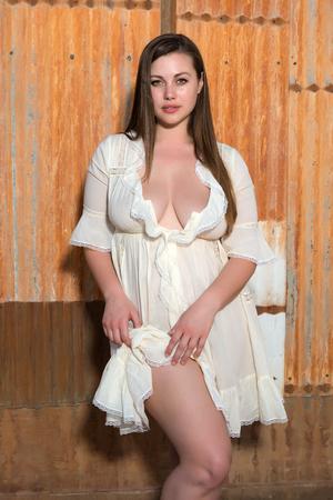 busty: Brunette bastante bien formada en un vestido de color amarillo pálido Foto de archivo