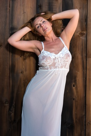 Beautiful tall redhead in a white lace negligee Banco de Imagens