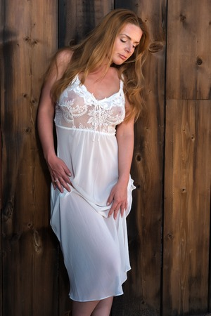 Beautiful tall redhead in a white lace negligee Stock Photo