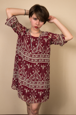 brick red: Pretty young brunette in a brick red print dress