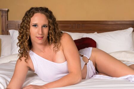 bed skirt: Pretty wavy haired brunette in a white blouse and skirt
