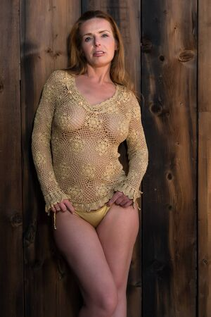 mature woman sexy: Beautiful tall redhead in a gold fishnet top Stock Photo