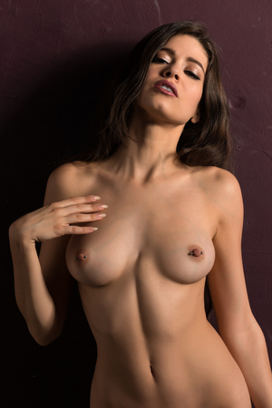 Tall slender brunette nude on a purple wall