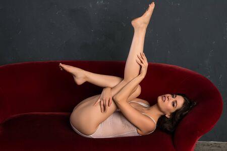 couch: Tall slender brunette in a white fishnet bodysuit Stock Photo