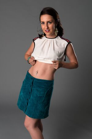 white blouse: Pretty young brunette in a white blouse and teal satin skirt