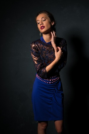 Pretty petite brunette in a blue wrap dress and a metallic jacket Stock Photo