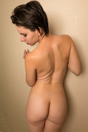 Pretty young brunette standing nude in a shower stall Stock Photo