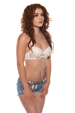 Petite redhead in a white bra and Stars and Stripes shorts