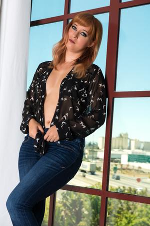 Pretty young redhead standing at a loft window Banco de Imagens