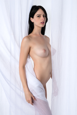 nudity: Tall slender brunette standing nude against a white curtain Stock Photo