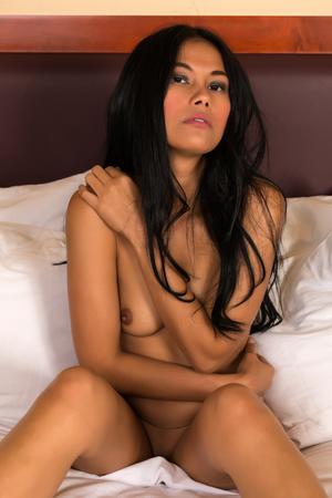 Beautiful petite Filipino woman nude in bed