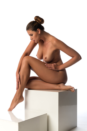 Statuesque young brunette nude on white blocks