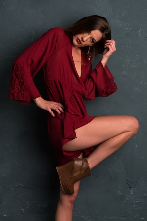 pretty brunette woman: Tall slim brunette dressed in a red wrap dress Stock Photo