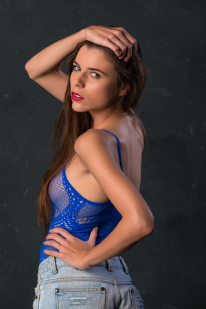 Beautiful slender young brunette dressed in blue