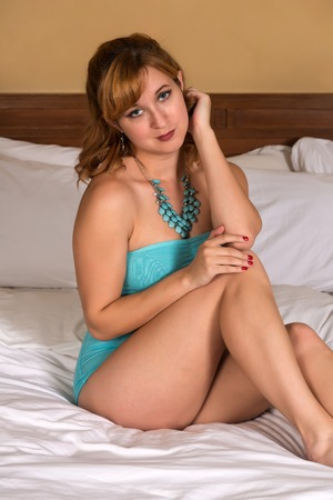 Pretty young redhead in a turquoise bodysuit Stock Photo