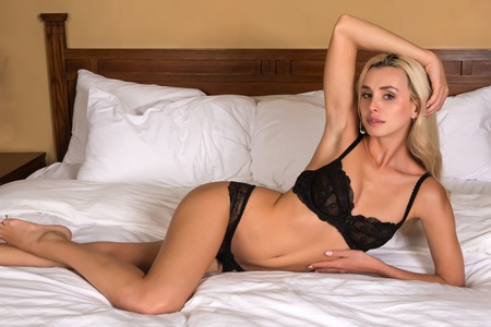 Beautiful petite blonde woman in black lingerie