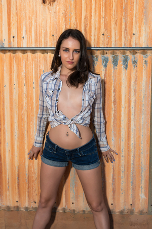 Pretty young brunette in a plaid shirt and denim shorts