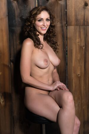 Beautiful shapely brunette nude against a wooden wall Stock Photo