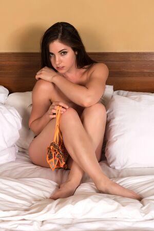 Pretty petite brunette in orange lingerie Stock Photo