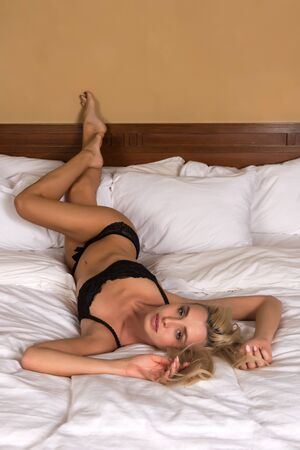 undergarment: Beautiful petite blonde woman in black lingerie