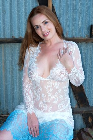 Beautiful tall redhead in a sheer white and blue gown