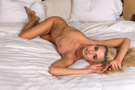 Beautiful petite blonde woman lying nude in bed Stock Photo - 68108426