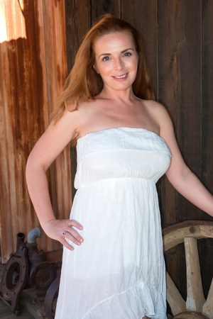 Beautiful tall redhead in a strapless white dress Stock Photo