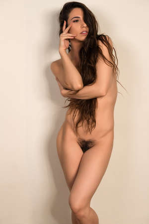 Pretty young brunette nude on a beige wall