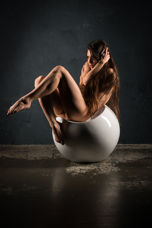 Pretty young brunette sitting nude on a white ball-shaped seat