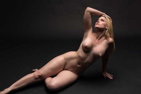 mujer rubia desnuda: Tall mujer rubia bien proporcionada desnuda acostada sobre fondo gris