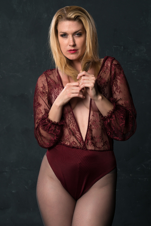 Tall shapely blonde woman in a sheer red bodysuit